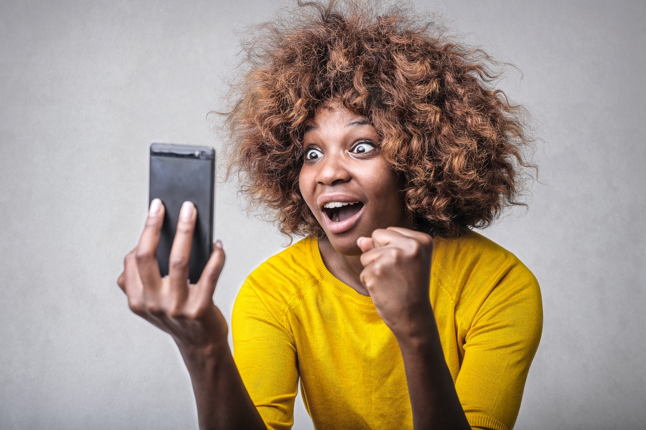 woman surprised holding a smartphone